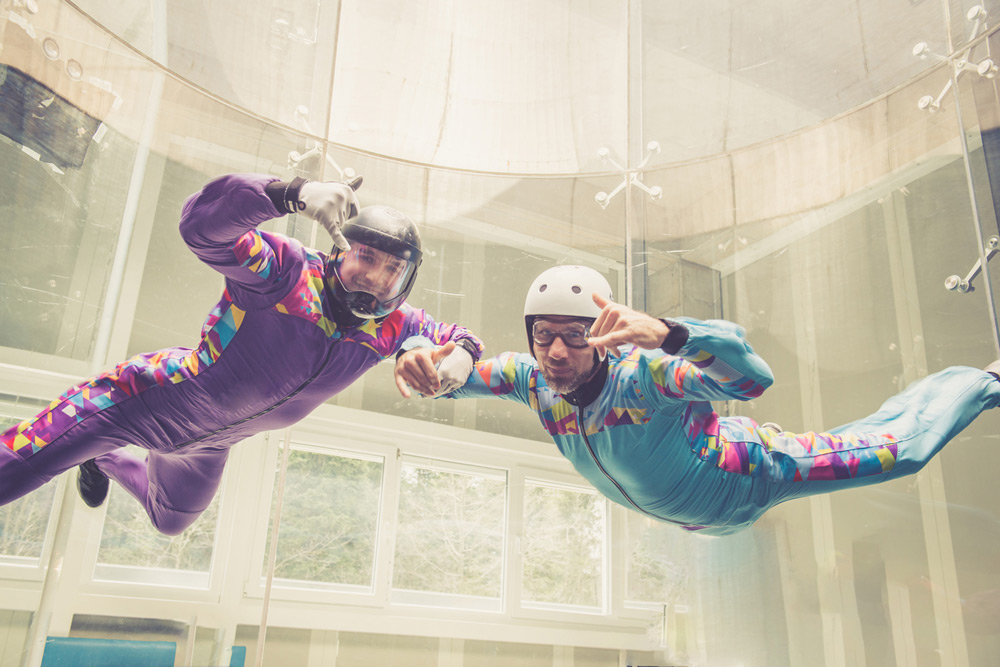 Man experiencing indoor skydiving with instructor